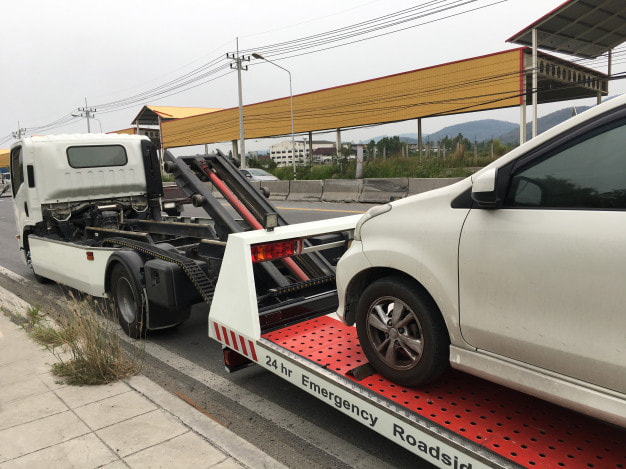 white car pulled by a white tow truck